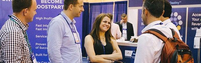 HostingCon attendees talk in exhibit hall