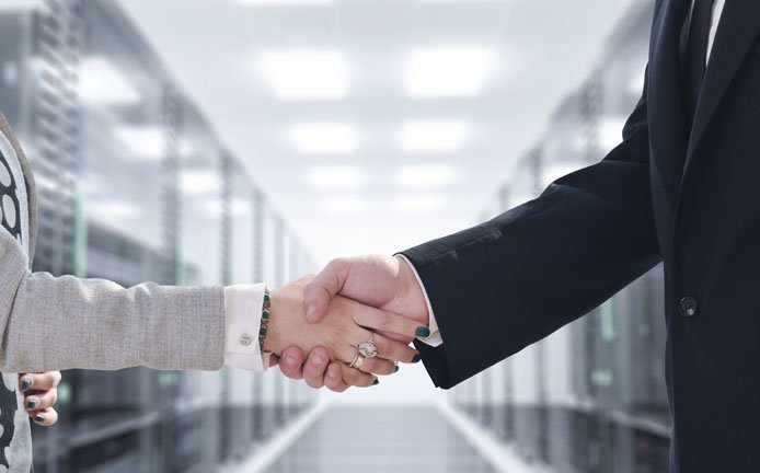 Photo of business people shaking hands in a datacenter