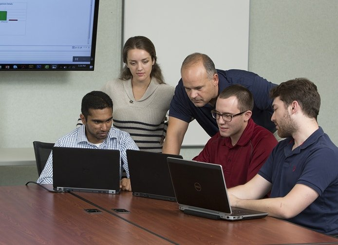 Photo of people collaborating around computers