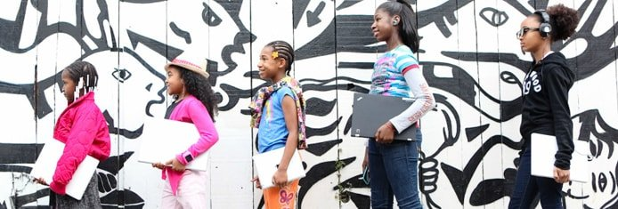 Image of black girls walking in front of graffiti with laptops
