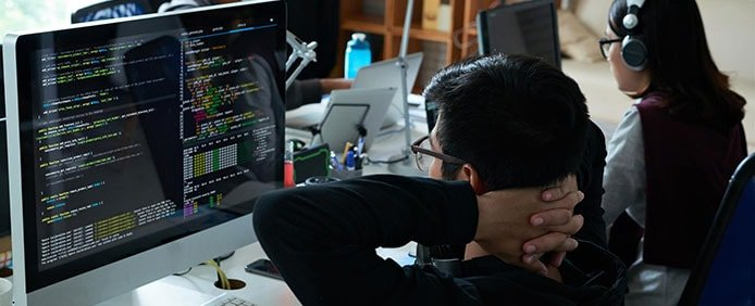 Image of developers sitting in front of code