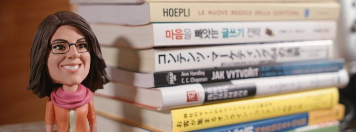 A photo of an Ann Handley bobblehead and her books in various languages