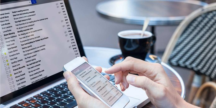 Image of woman checking email on her laptop and phone