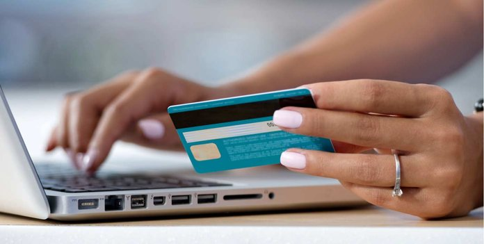 Image of someone holding a credit card to make a payment on a laptop