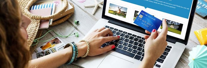 Image of woman holding a credit card near a laptop