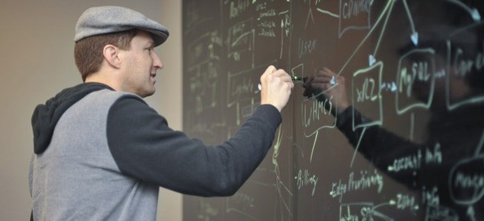 Image of Nathan Moore sketching out plans on a chalkboard