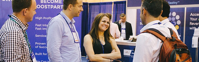 HostingCon attendees talk in exhibit hall