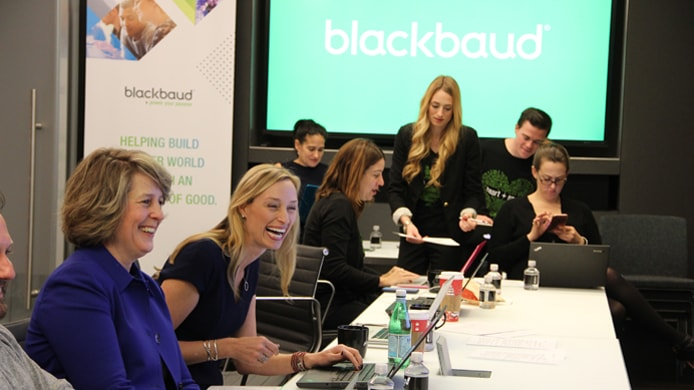Photo of Blackbaud employees in a board room