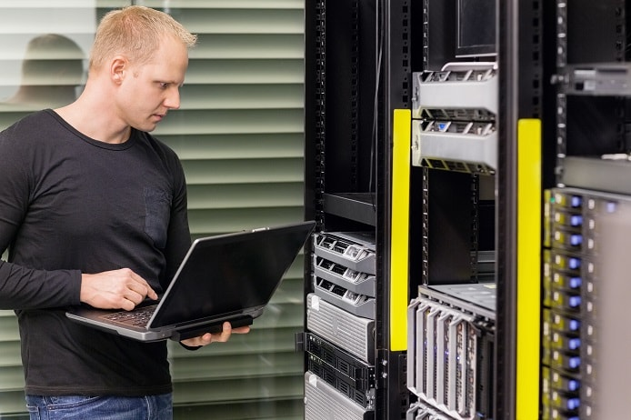 Stock photo of datacenter admin monitoring servers