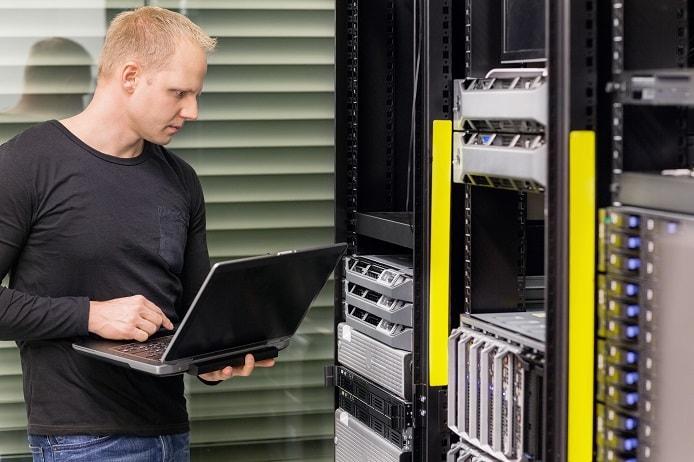 Stock photo of datacenter admin monitoring servers