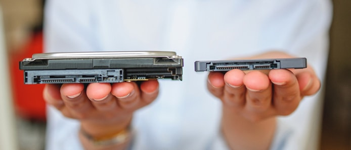 Person holding an SSD and HDD