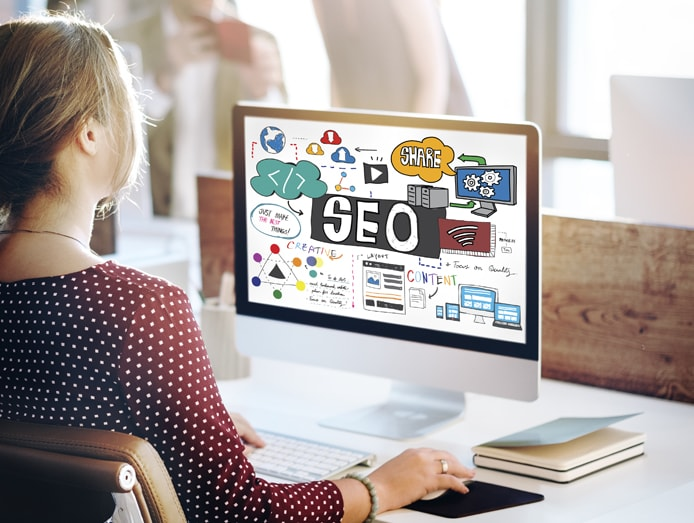 Photo of a woman at a computer with SEO concepts on the screen