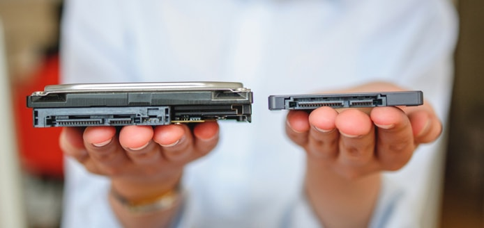 Person holding a hard disk drive and solid-state drive