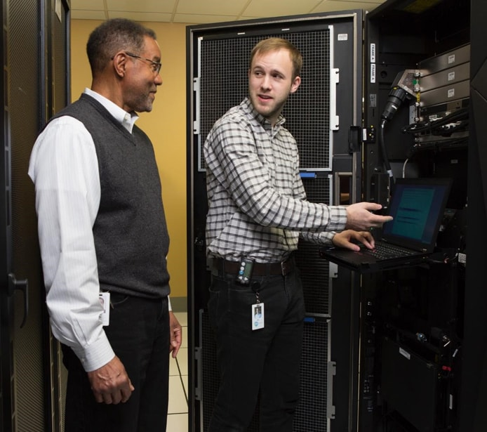 Photo of two men talking near a mainframe