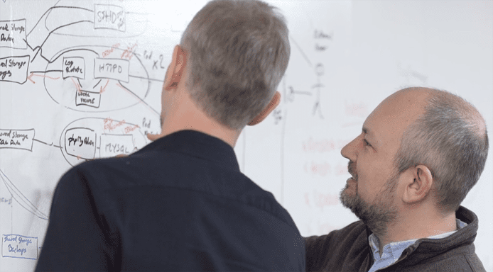 Photo of IT pros looking at a whiteboard with systems architecture blueprints