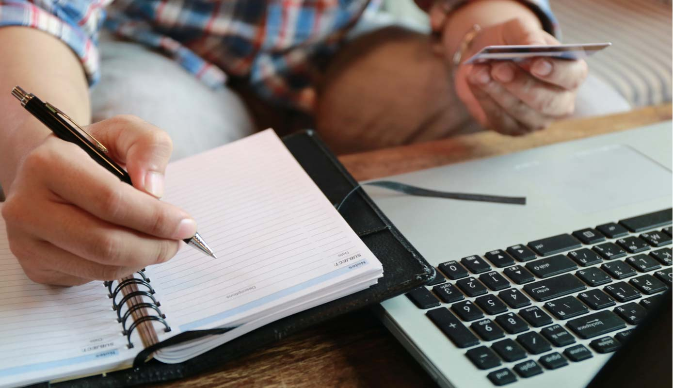 Image of someone making an online payment next to a notebook