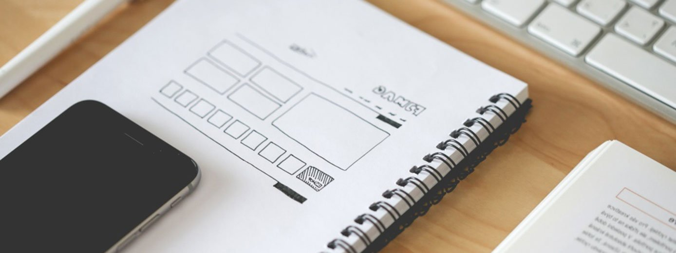 Image of wireframe website design next to a phone